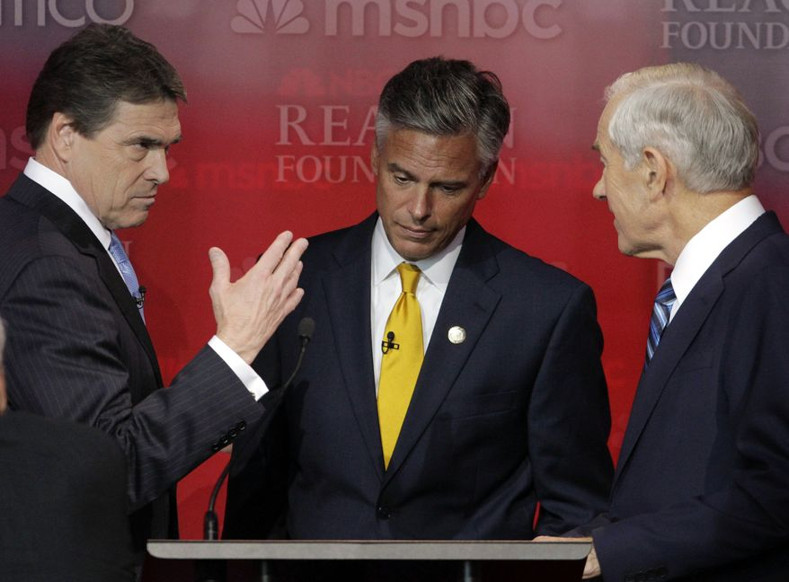 Texas Gov. Rick Perry (left), former Utah Gov. Jon Huntsman (center) and Rep. Ron Paul, Texas Republican, talk Sept. 7, 2011, during a break at the Republican presidential candidate debate at the Reagan Library in Simi Valley, Calif. (Associated Press)