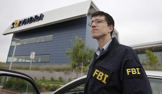 FBI agents stand guard outside the headquarters of Solyndra, a solar firm in Fremont, Calif., on Sept. 8, 2011. (Associated Press)