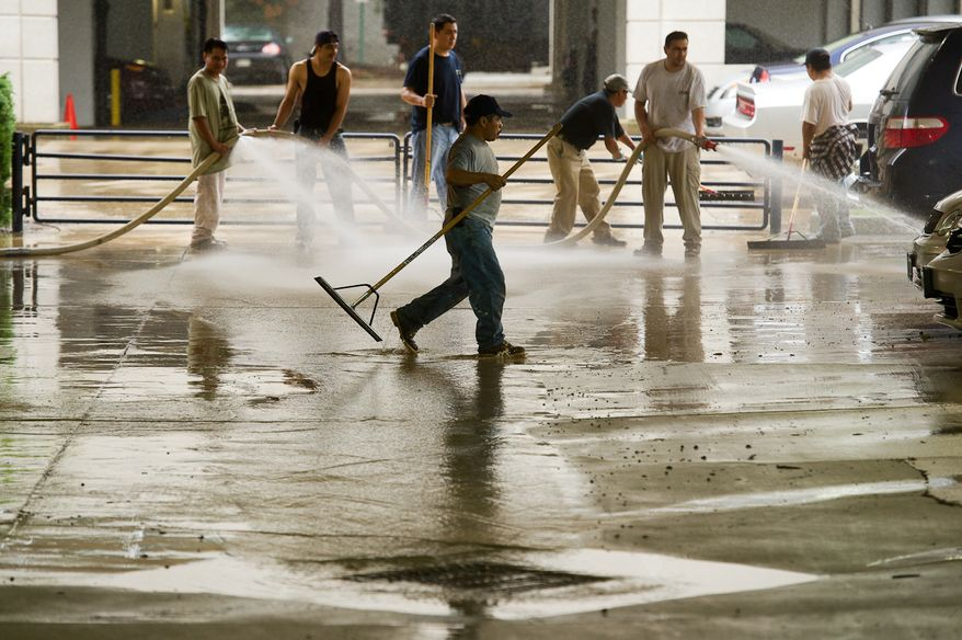 A cleaning crew removes mud from an office building's parking lot on Eisenhower Avenue in Alexandria, Va., on Sept. 9, 2011. The lot was flooded after heavy rains pounded the region the previous night. (Andrew Harnik/The Washington Times)
