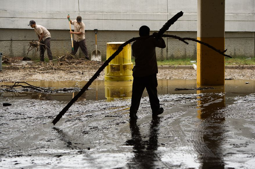 A clean-up crew collects tree limbs and debris that washed into the parking lot on Eisenhower Avenue in Alexandria, Va., on Sept. 9, 2011. The lot was flooded after heavy rains pounded the region the previous night. (Andrew Harnik/The Washington Times)