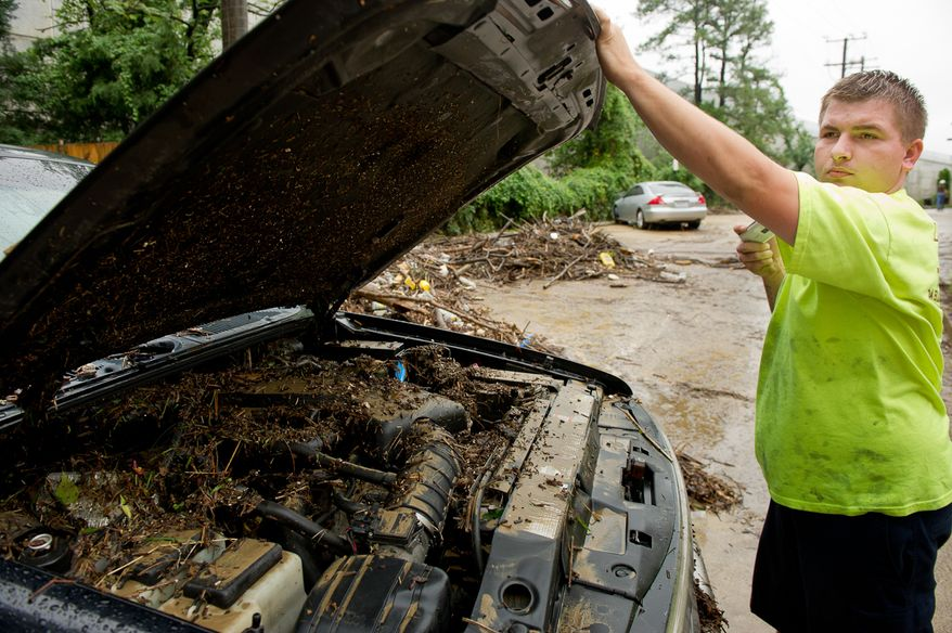 Tow truck driver Terry Walker takes photos of a vehicle's muddy engine on Eisenhower Avenue in Alexandria, Va., on Sept. 9, 2011, after heavy rains pounded the region the previous night. (Andrew Harnik/The Washington Times)