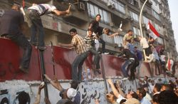 Some hundreds of Egyptian activists demolish a concrete wall around a building housing the Israeli embassy in Cairo, Egypt, to protect it against demonstrators, Friday, Sept. 9, 2011. (AP Photo/Amr Nabil)