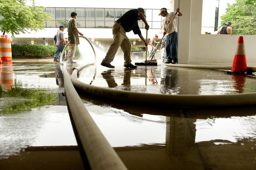 A cleaning crew removes mud from the first-floor parking lot at Alexandria Tech Center II on Eisenhower Avenue in Alexandria, Va., on Sept. 9, 2011. The lot was flooded after heavy rains pounded the region the previous night. (Andrew Harnik/The Washington Times)