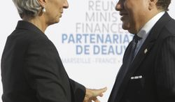 International Monetary Fund (IMF) managing director Christine Lagarde, left, talks with Tunisian Finance Minister Jelloul Ayed during the group photo at the Deauville partnership meeting in Marseille, southern France, Saturday, Sept.10, 2011. (AP Photo/Lionel Cironneau)