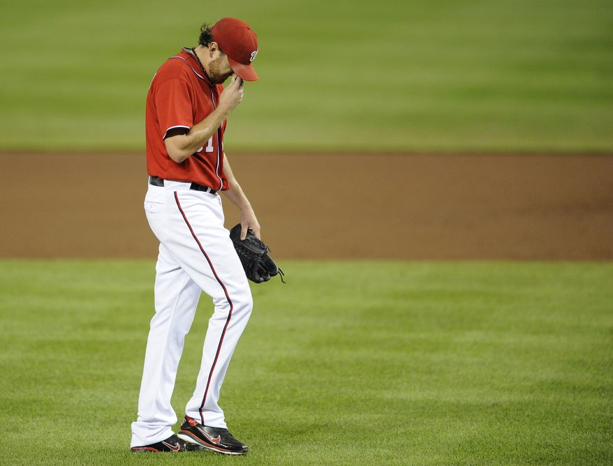 Washington Nationals starting pitcher John Lannan walks to the dugout after he was pulled from the baseball game against the Houston Astros during the third inning Saturday, Sept. 10, 2011, in Washington. (AP Photo/Nick Wass)