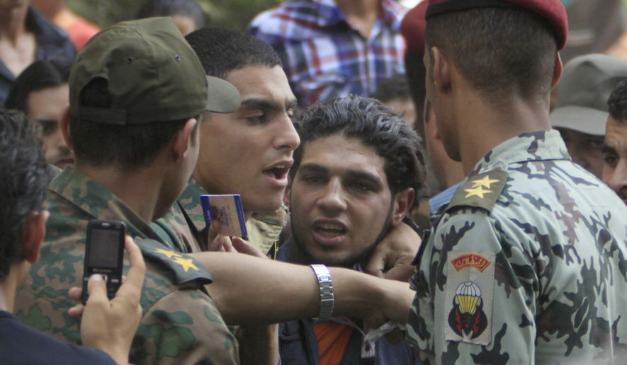 Egyptian army officers arrest a suspected demonstrator at the site of clashes between protesters and anti-riot policemen near the Israeli embassy in Cairo, Egypt, Saturday, Sept.10, 2011. (AP Photo/Amr Nabil)