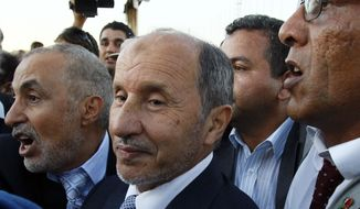 ** FILE ** Libyan Transitional National Council chairman Mustafa Abdul-Jalil (center), flanked by bodyguards, arrives at Metiga Airport in Tripoli, Libya, on Saturday, Sept. 10, 2011. (AP Photo/Francois Mori)