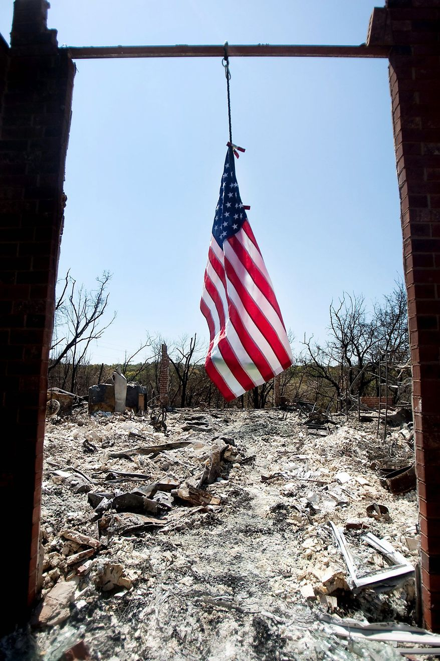 A flag hangs from the frame above the front door of a home on Medina River Way in Steiner Ranch in Austin, Texas, on Saturday. Texas is in the midst of one of its worst wildfire outbreaks in state history.