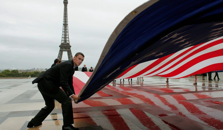 An American flag is unfurled Sunday near the Eiffel Tower in Paris to mark the decennial of the Sept. 11, 2001, attacks on the United States. From Moscow to Manila and elsewhere around the globe, somber observances paid tribute to those who lost their lives 10 years ago. (Associated Press)