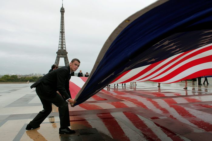 An American flag is unfurled Sunday near the Eiffel Tower in Paris to mark the decennial of the Sept. 11, 2001, attacks on the United States. From Moscow to Manila and elsewhere around the globe, somber o