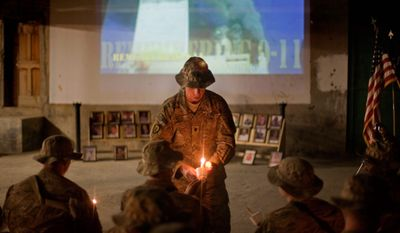 Lt. Col. Daniel Wilson lights a candle Sunday at Forward Operating Base Bostick in Kunar province, Afghanistan, in commemoration of the 10th anniversary of the attacks and the soldiers his Hawaii-based unit has lost since then in the wars in Iraq and Afghanistan. (Associated Press)