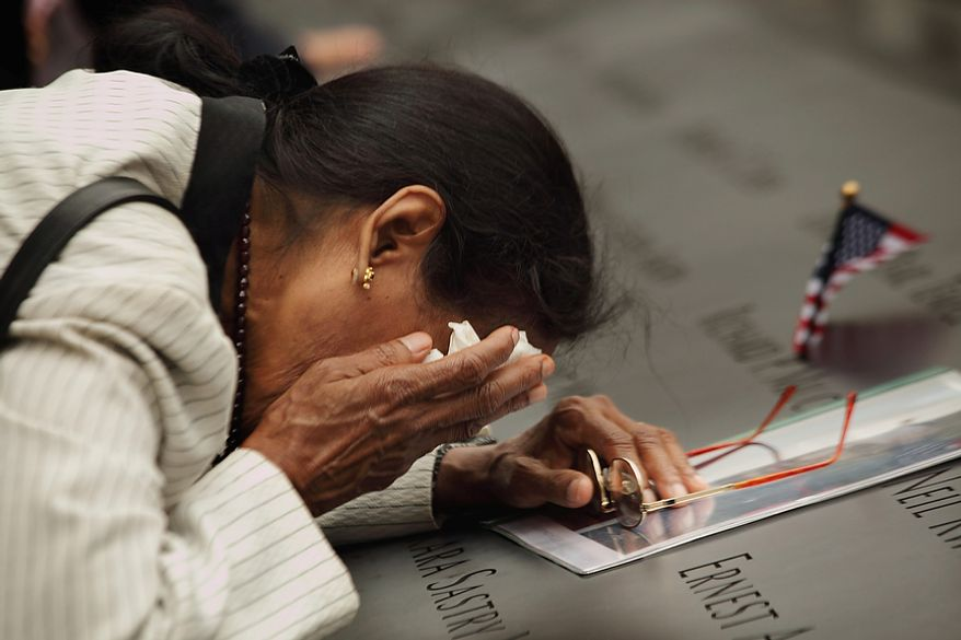 Vasantha Velamuri, who's husband, Sankara Sastry Velamuri, was killed in the 9/11 terrorist attacks on the World Trade Center, mourns at the place where his name is inscribed on the Sept. 11 memorial at the World Trade Center site in New York during a ceremony to mark the 10th anniversary of the attacks Sunday, Sept. 11, 2011. (AP Photo/Carolyn Cole, Pool)