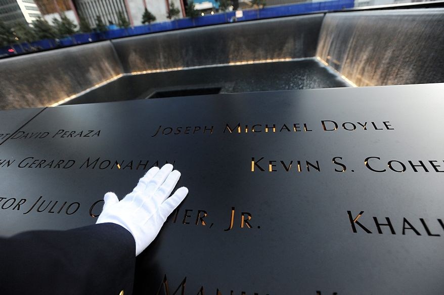 A police officer's white-gloved hand touches names on the wall surrounding the north pool of the 9/11 Memorial during the tenth anniversary ceremony at the site of the World Trade Center, Sunday Sept. 11, 2011, in New York. (AP Photo/David Handschuh, Pool)