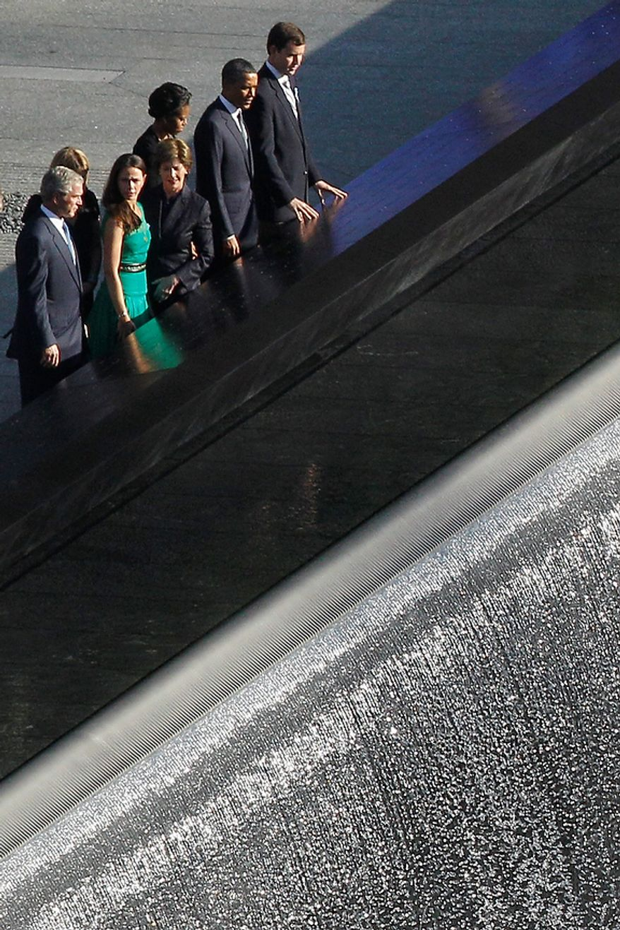Former President George W. Bush, left, and former first lady Laura Bush, along with President Barack Obama, second from right,  and first lady Michelle Obama along with others, marking the 10th anniversary of the Sept. 11 attacks, pay their respects at the National September 11 Memorial at the World Trade Center site in Sunday, Sept. 11, 2011, in New York. (AP Photo/Matt Rourke)