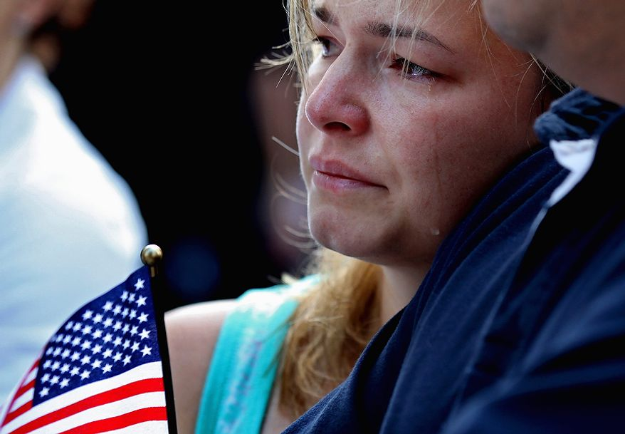 Jacqueline Arana, of Union City, N.J., sheds a tear at 8:46 a.m., marking when the first plane hit the World Trade Center in 2001, during a ceremony in Lower Manhattan, Sunday, Sept. 11, 2011, marking the 10th anniversary of the attacks at the World Trade Center. (AP Photo/Craig Ruttle)