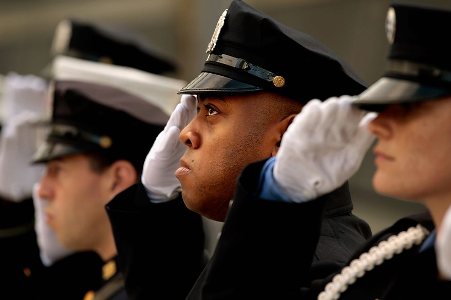 "New York City police and firefighters, and Port Authority of NY & NJ police officers salute during the singing of the ""Star Spangled Banner"" at the Sept. 11 memorial, during 10th anniversary ceremonies at the site, Sunday, Sept. 11, 2011, in New York. (AP Photo/Chip Somodevilla, Pool)"