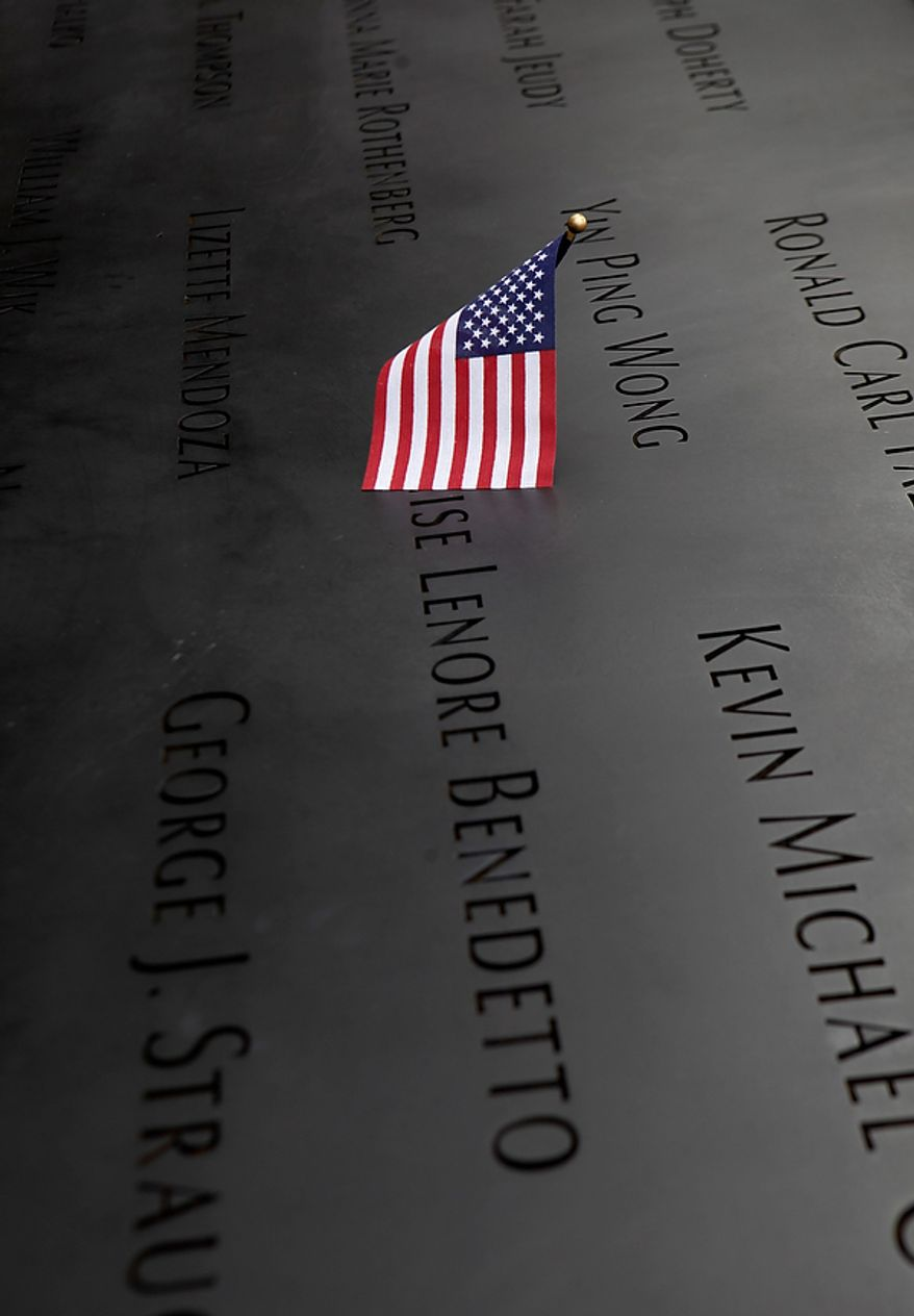 A flag rests on a panel inscribed with the names of those killed on 9/11 at the National September 11 Memorial at the World Trade Center site in New York, Sunday, Sept. 11, 2011. (AP Photo/Seth Wenig, Pool)