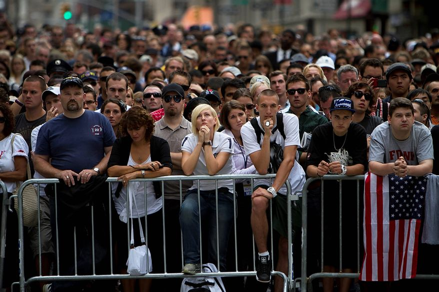People gather during a ceremony marking the 10th anniversary of the attacks on the World Trade Center Sunday, Sept. 11, 2011, outside the World Trade Center site in New York. (AP Photo/Oded Balilty)