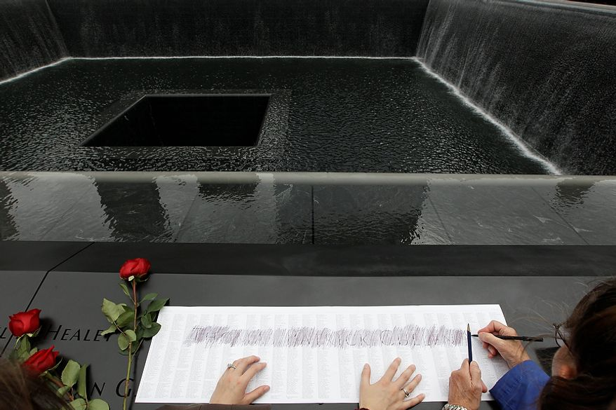 Rita Cullen, right, traces her son firefighter Tom Cullen's name from the engraving at the south pool of the National September 11 Memorial during a ceremony marking the 10th anniversary of the attacks at World Trade Center, Sunday, Sept. 11, 2011 in New York. (AP Photo/Mary Altaffer)