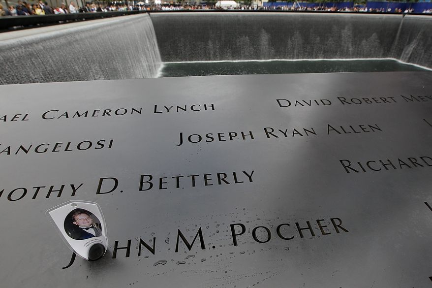 A prayer card for John Pocher is placed on his name engraved at the north pool of the National September 11 Memorial during a ceremony marking the 10th anniversary of the attacks, Sunday, Sept. 11, 2011 at the World Trade Center site in New York.  (AP Photo/Mary Altaffer)
