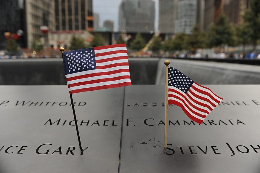 American flags adorn the edge of the south pool of the Sept. 11 memorial at the World Trade Center site in New York Sunday, Sept. 11, 2011. (AP Photo/Aaron Showalter, Pool)