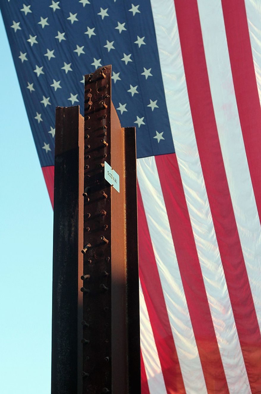 Metal beams taken from the World Trade Center stand in front of an American flag during a memorial ceremony to commemorate the 10th anniversary of the September 11, 2001, terrorist attacks in New York City and Washington D.C. Sunday, Sept. 11, 2011, at Parc Sans Souci in downtown Lafayette, La. (AP Photo/Leslie Westbrook September 11, 2011