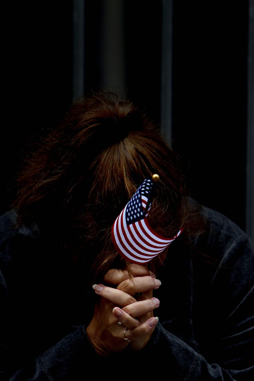 A woman pays her respects during a ceremony marking the 10th anniversary of the Sept. 11 terrorist attacks on the World Trade Center, Sunday, Sept. 11, 2011, outside the World Trade Center site in New York.  (AP Photo/Oded Balilty)