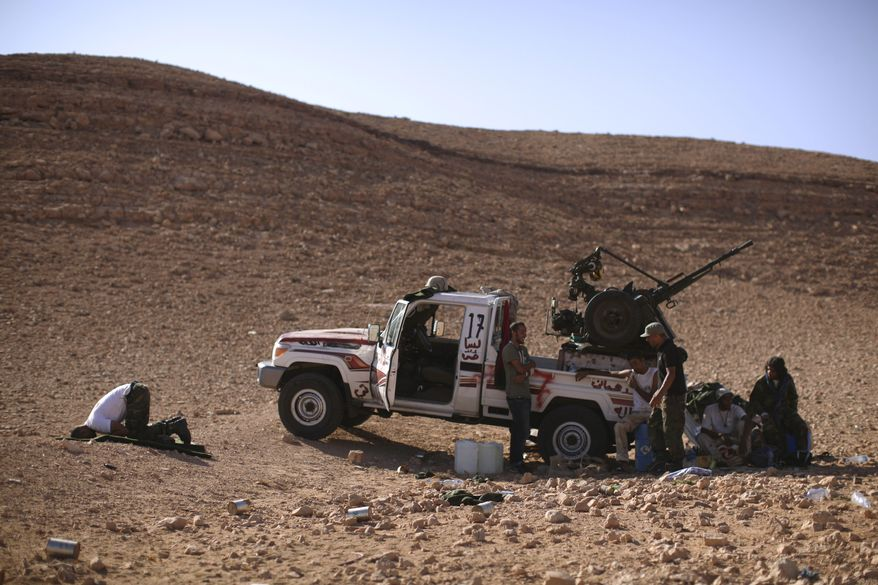 Rebel fighter Ahmed Hamza (left), a 23-year-old former engineering student, prays on the outskirts of Bani Walid, Libya, on Sunday, Sept. 11, 2011. Libyan fighters are signing up for a final assault on one of the last remaining bastions of support for Col. Moammar Gadhafi. (AP Photo/Alexandre Meneghini)