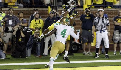 Michigan wide receiver Roy Roundtree catches the game-winning touchdown pass over Notre Dame cornerback Gary Gray during the closing seconds of the fourth quarter of an NCAA in Ann Arbor, Mich. on Saturday, Sept. 10, 2011. Michigan won 35-31.(AP Photo/Carlos Osorio)