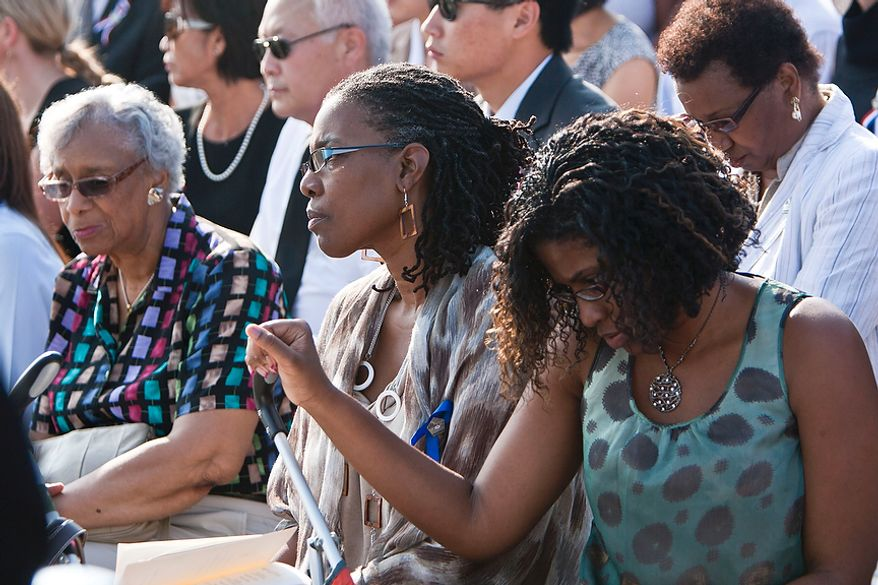 """Faye Colbert (left), with daughter Sheila Moody (center) and granddaughter Qiana Black, all of Severn, Md., observe a moment of silence on Sunday, Sept. 11, 2011, at the Pentagon Memorial in Arlington during the commemoration of the Sept. 11, 2001, attack on the Defense Department headquarters. Ms. Moody is a survivor of the attack; her office was located just below the point that Flight 77 struck the building. """"It's good to come back,"""" Ms. Moody said, """"but it's been a blessing to survive, to see my granddaughter."""" She admires the other families who suffered a loss in the attack for their ability to thrive in spite of such sadness. (T.J. Kirkpatrick/The Washington Times)"""