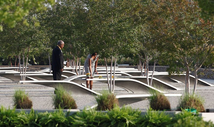 A woman lays a sunflower on a bench honoring a victim of the Sept. 11 attack on the Pentagon as the 10th anniversary of the event is observed at the Pentagon outside Washington on Sunday, Sept. 11, 2011. (AP Photo/Charles Dharapak)