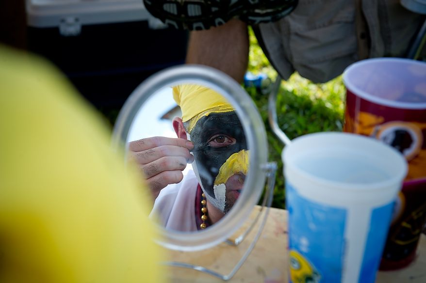 Mike Mayer of Gaithersburg, Md. paints his face in the parking lot while tailgating before the Washington Redskins play the New York Giants at FedEx Field in Landover, Md. Sunday, September 11, 2011. (Rod Lamkey Jr. / The Washington Times)
