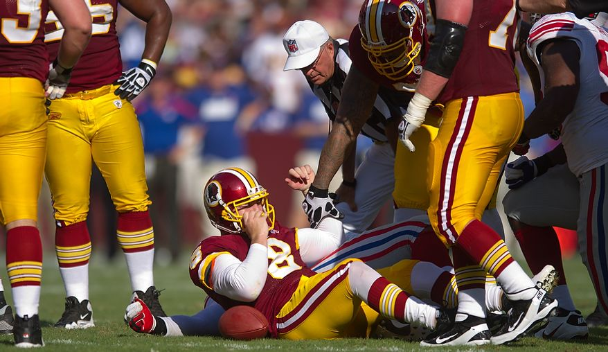 Washington Redskins QB Rex Grossman (8) is slow to get up after a 5 yard sack by the New York Giants during the 1st quarter at FedEx Field in Landover, Md. Sunday, September 11, 2011. (Andrew Harnik / The Washington Times)