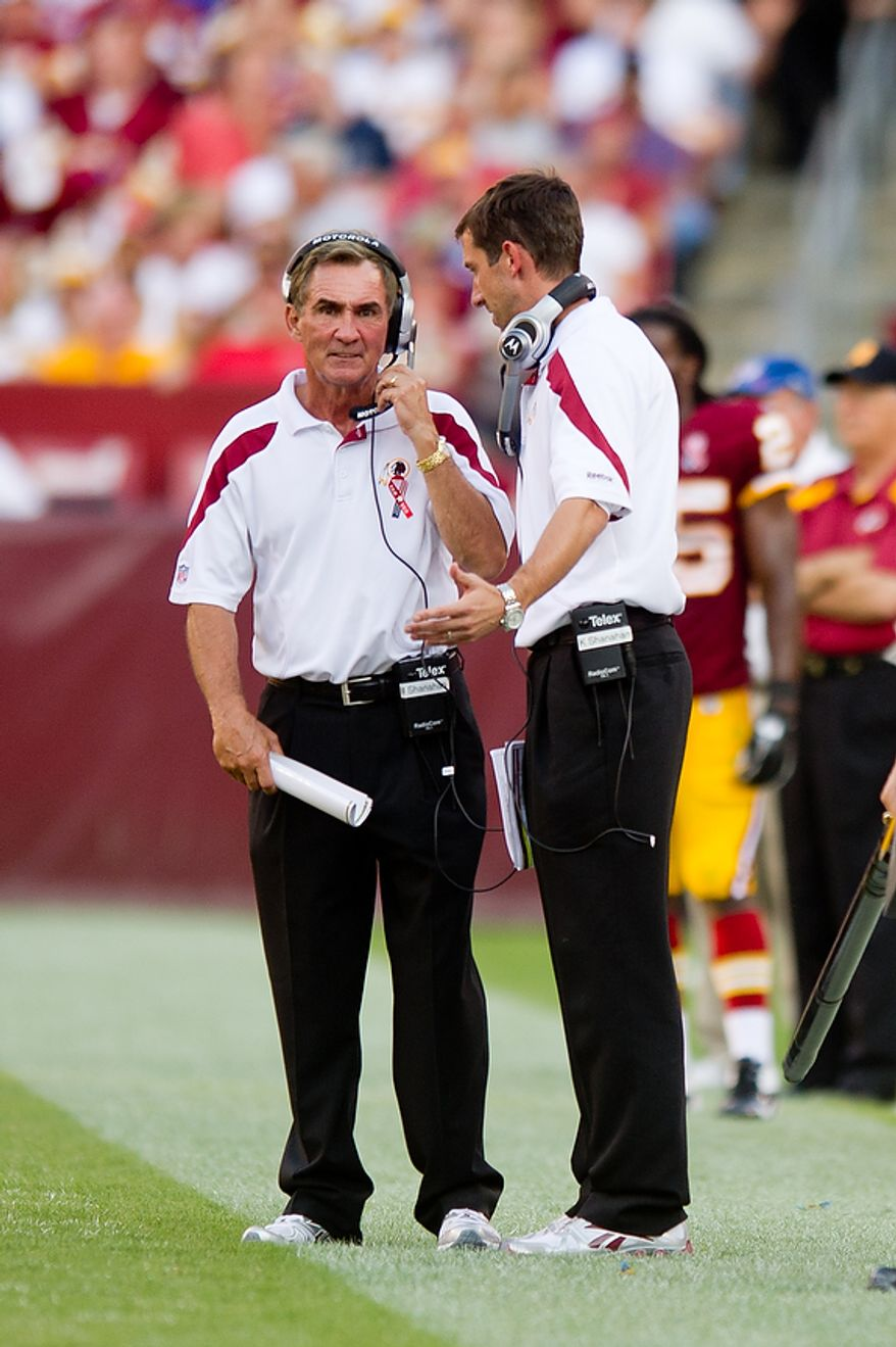 Washington Redskins head coach Mike Shanahan (left) speaks on the sidelines with son and offensive coordinator Kyle Shanahan (right) as their team plays the New York Giants during the 3rd quarter at FedEx Field in Landover, Md. Sunday, September 11, 2011. (Andrew Harnik / The Washington Times)