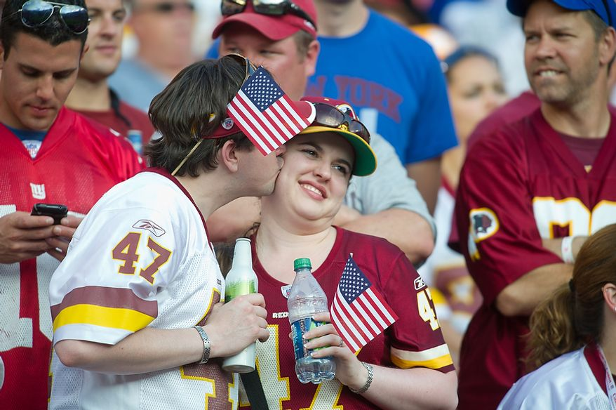 Washington Redskins share a kiss in the stands as their team leads the New York Giants during the 3rd quarter at FedEx Field in Landover, Md. Sunday, September 11, 2011. (Rod Lamkey Jr. / The Washington Times)