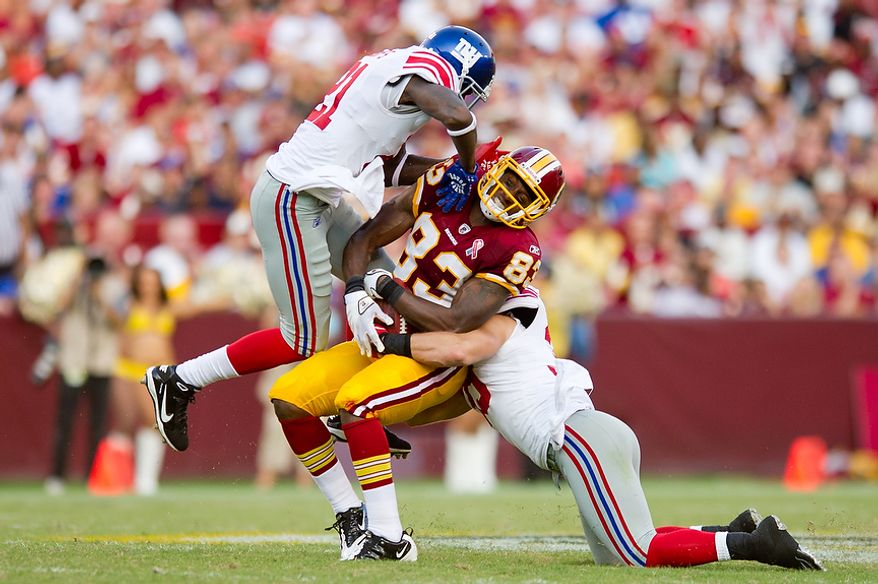 Washington Redskins TE Fred Davis (83) is taken out by New York Giants S Kenny Phillips (21) and S Tyler Sash (39) after a gain of 28 yards during the 3rd quarter at FedEx Field in Landover, Md. Sunday, September 11, 2011. (Andrew Harnik / The Washington Times)