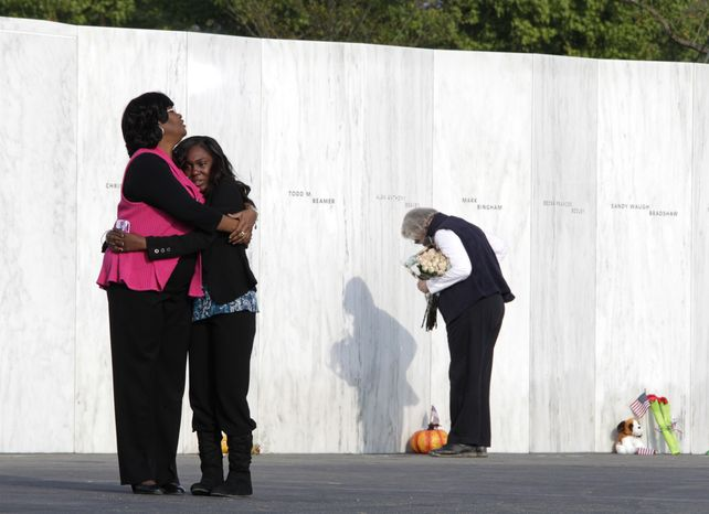 Visitors embrace in front of the Wall of Names near the crash site of Flight 93 in Shanksville, Pa., on Sunday, Sept. 11, 2011. (AP Photo/Amy Sancetta)