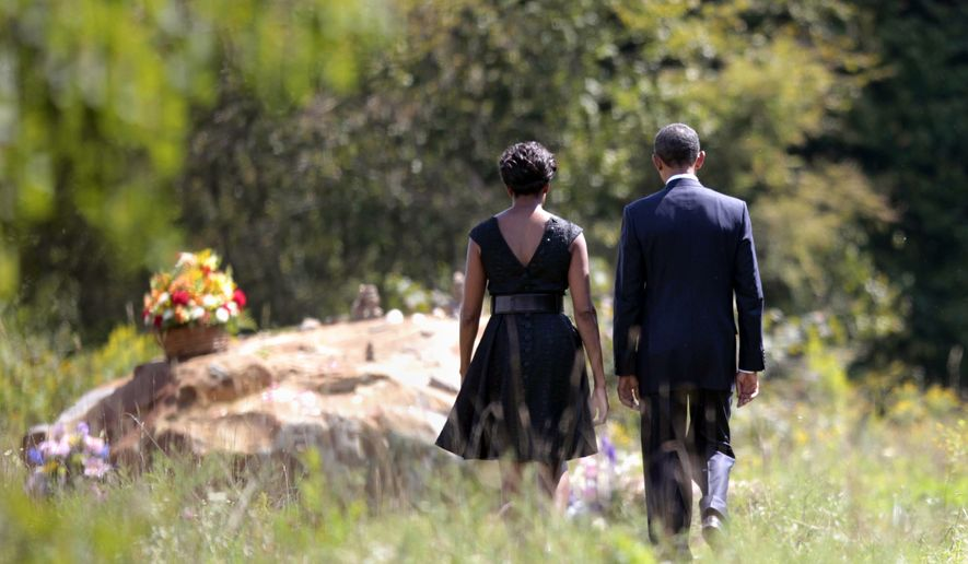 President Obama and first lady Michelle Obama walk to the crash site of Flight 93 during their visit to the Flight 93 National Memorial on Sunday, Sept., 11, 2011, in Shanksville, Pa., on the 10th anniversary the attacks. (AP Photo/Pablo Martinez Monsivais)