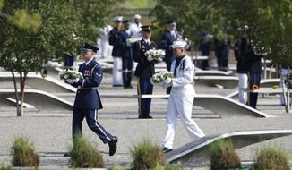 An honor guard carries wreaths at the Pentagon Memorial outside the Defense Department headquarters in Arlington on Sunday, Sept. 11, 2011, to mark the 10th anniversary of the 9/11 attacks. (AP Photo/Charles Dharapak)