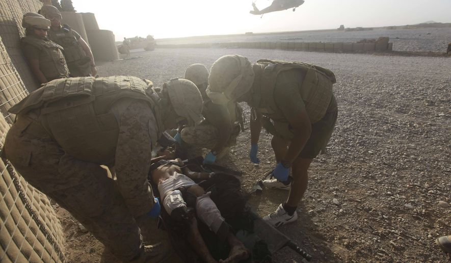 U.S. Marine medics examines a wounded Afghan boy after he was wounded in an explosion at Forward Operating Base Edi in the Helmand Province of southern Afghanistan, Saturday, Sept. 10, 2011.(AP Photo/Rafiq Maqbool)