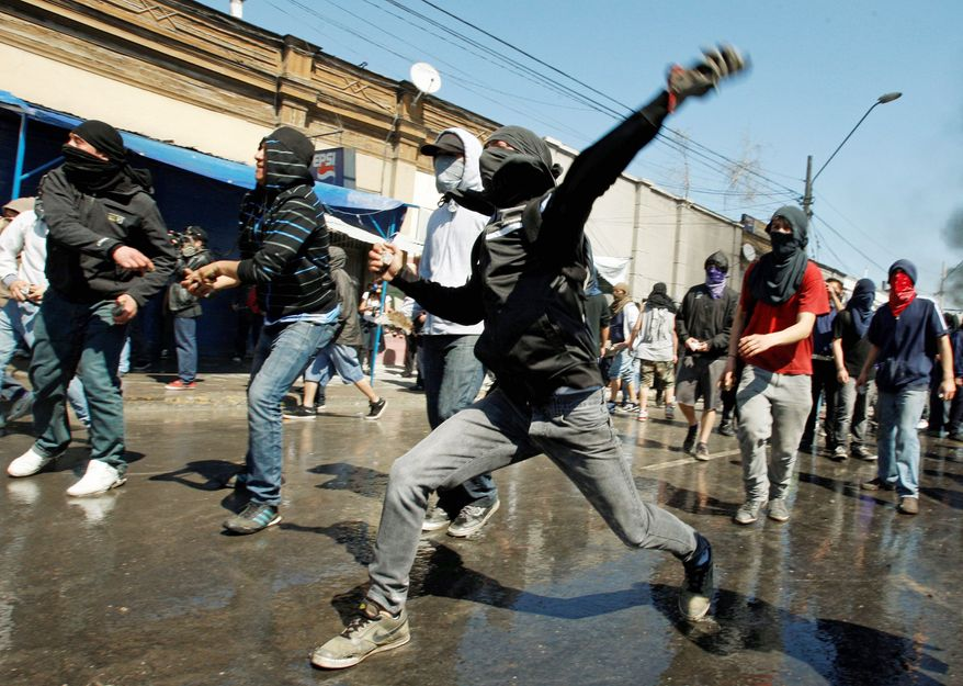 Protesters in Santiago, Chile, throw stones at police Sunday after a march marking the 38th anniversary of Chile's military coup. Police arrested 280 people and 45 people were injured, including a teenager who is in critical condition. (Associated Press)