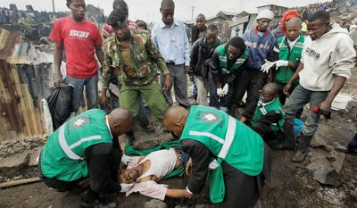 Joseph Mwangi is aided by ambulance workers as he cries in shock after seeing the charred remains of two of his children where his home once stood. (Associated Press)