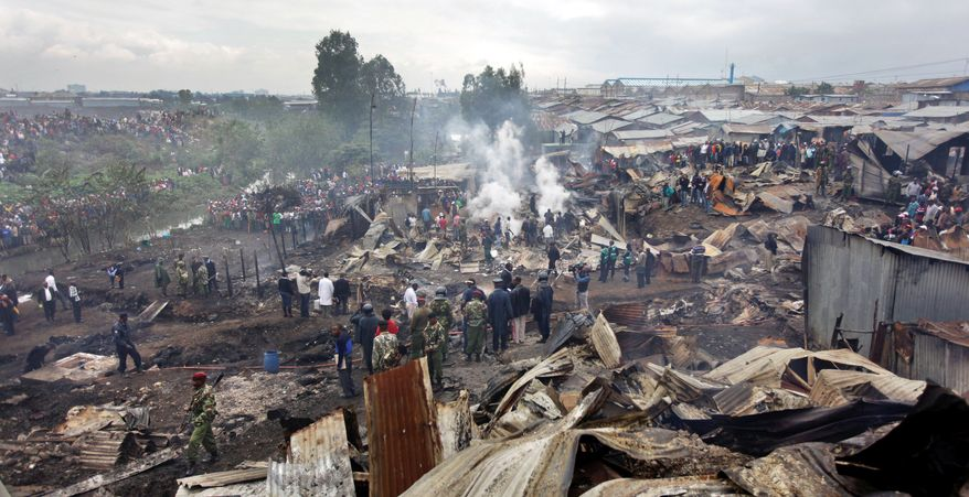 Townspeople watch as rescue workers tend to the injured and dead in flattened homes after a gasoline pipeline exploded Monday in Nairobi, Kenya. At least 75 people were dead and the toll was expected to rise; more than 100 suffered severe burns. (Associated Press)