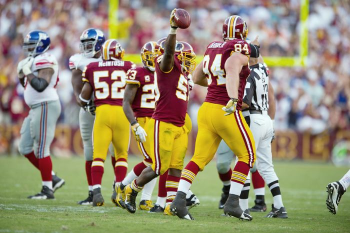 """Linebacker London Fletcher (holding ball), who joined the Redskins in 2007, said, """"You enjoy coming to work. That hasn't always been the case."""" (Andrew Harnik/The Washington Times)"""