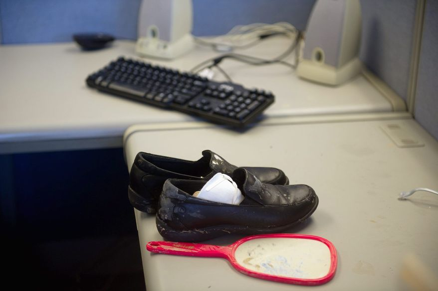 A pair of shoes and a mirror sit on the desk in an office cubicle at the administration building. Employees moved documents from the building for safekeeping. (Andrew Harnik/The Washington Times)