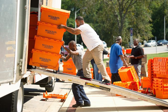 Abdul Lawson (on ramp) and Ricky Layfield move crates of government files from the flooded Prince George's County Administration Building into a truck to be temporarily stored. The building is expected to reopen Tuesday. (Andrew Harnik/The Washington Times)