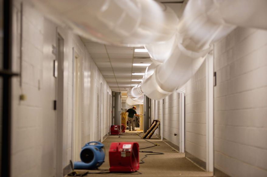 A worker labors in a hallway of the administration building in Prince George's County as large dehumidifying tubes do their work in drying out the building for an expected reopening on Tuesday. (Andrew Harnik/The Washington Times)
