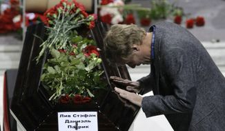 """A mourner bows at the coffin of Swedish professional ice hockey player Stefan Liv in the Arena in Yaroslavl, Russia, northeast of Moscow, on Saturday, Sept. 10, 2011, during a funeral service for the victims of Wednesday's plane crash. The sign on the coffin reads """"Stefan Daniel Patryk Liv."""" (AP Photo/Misha Japaridze)"""