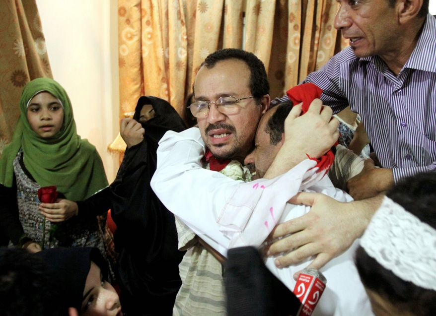 Dr. Ali al-Ekri (center) embraces an unidentified man at Dr. al-Ekri's home Sept. 7 in Daih, Bahrain. He was one of several medical workers released from jail that day. (Associated Press))
