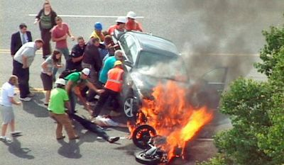 In this image taken from video Monday, a group of people tilt a burning BMW to free Brandon Wright (on his back on the ground), who was pinned underneath after he collided with the car while riding his motorcycle in Logan, Utah. (Associated Press)